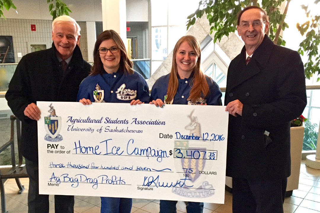 Home Ice Campaign chair Dave King (far left) and lead donor Merlis Belsher (far right) presented with a donation to the Home Ice Campaign by members of the Agricultural Student Association, Bayley Blackwell and Jacqueline Toews.
