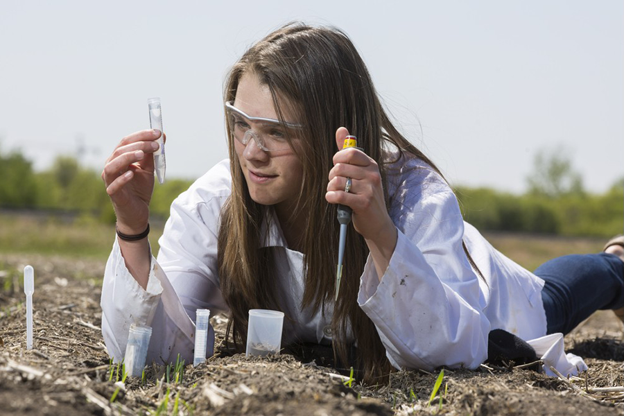 Alexis Adams, who recently defended her master's thesis, takes soil samples (photo by David Stobbe).