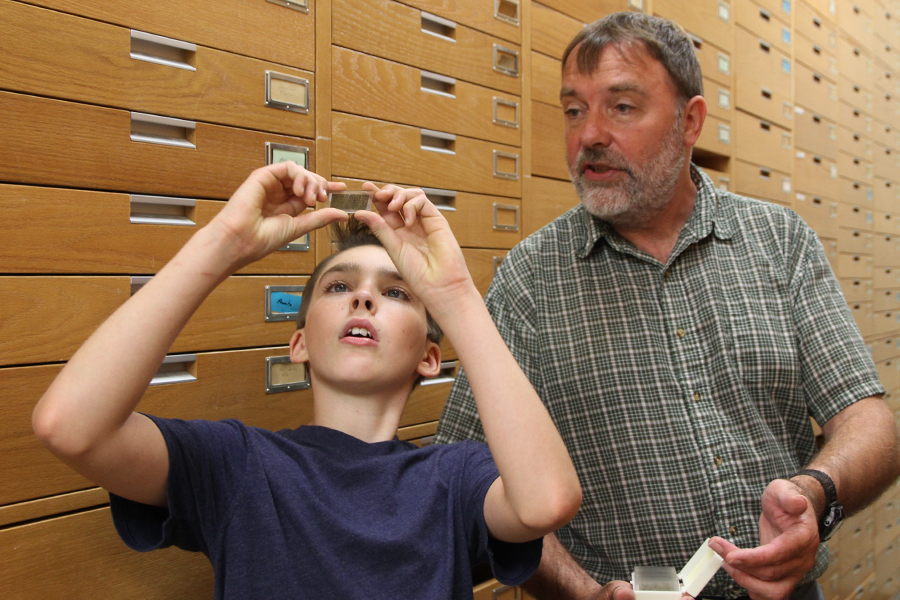 Twelve year-old Judah Tyreman examines rock specimens in the basement of the Geology Building alongside Kevin Ansdell, a professor in the Department of Geological Sciences.