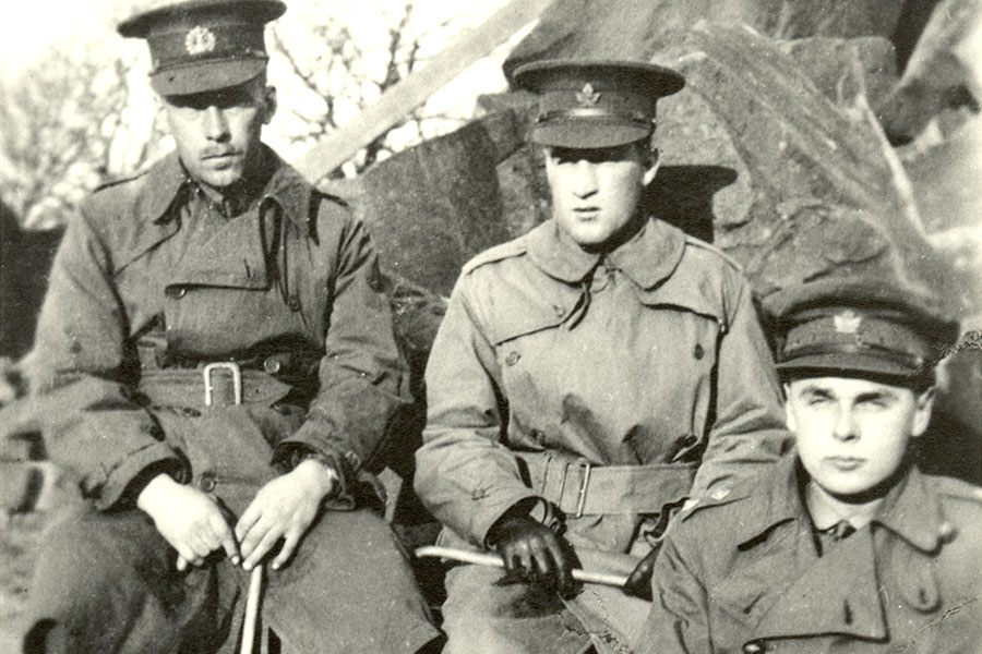 Left to right: John Einarson from Yorkton, Allan Macmillan and John Diefenbaker seated on rocks holding canes in England.