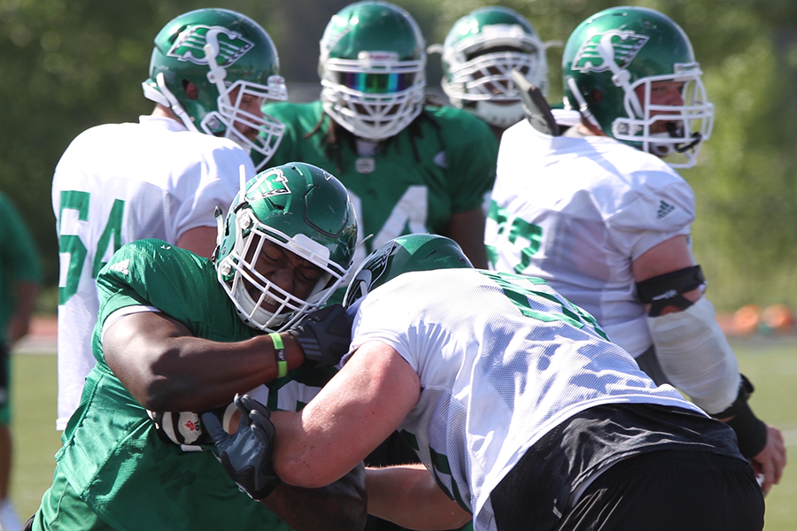 Former Huskie Tim Agbaje (left) rushing the passer during a drill in Roughriders training camp (photo by James Shewaga).