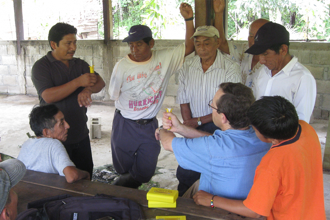 James Waldram (blue shirt, centre) demonstrates a safe way to remove snake venom while meeting with traditional Maya healers in Belize.