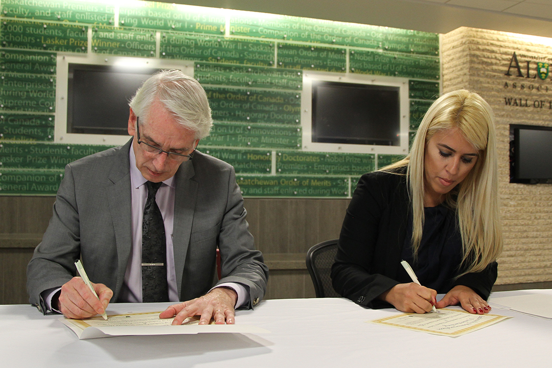 Peter Stoicheff and Renata Huyghebaert sign a MOU to work on sustainability initiatives on campus.