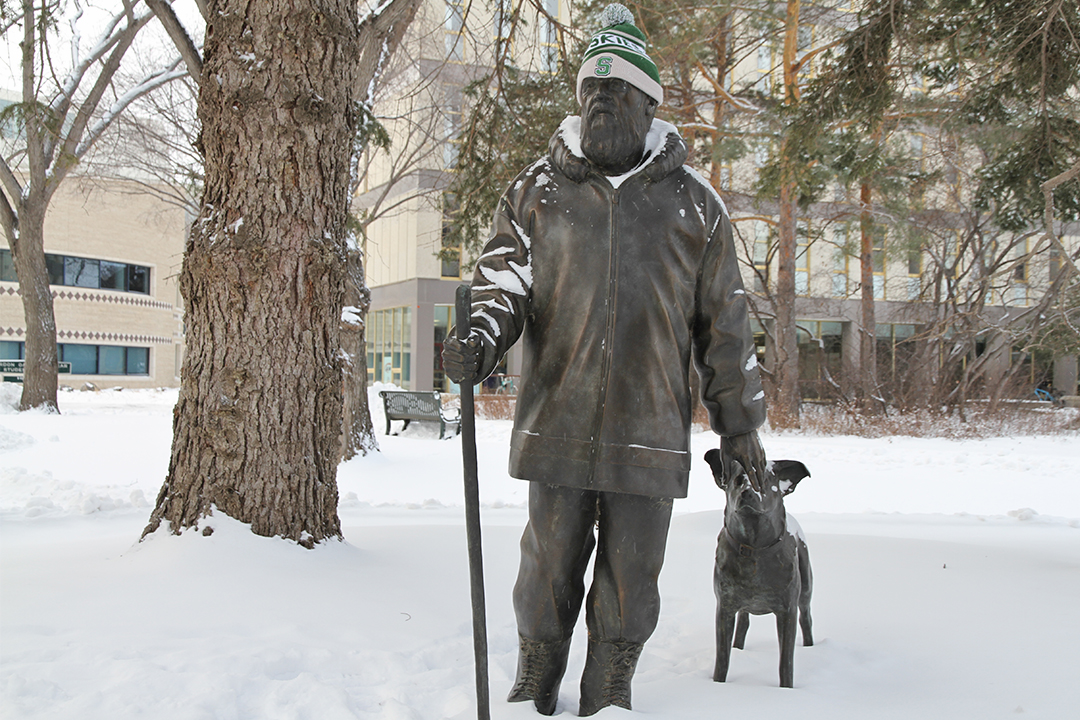 Farley Mowat keeps an eye on the wintery U of S campus alongside his dog, Chester.